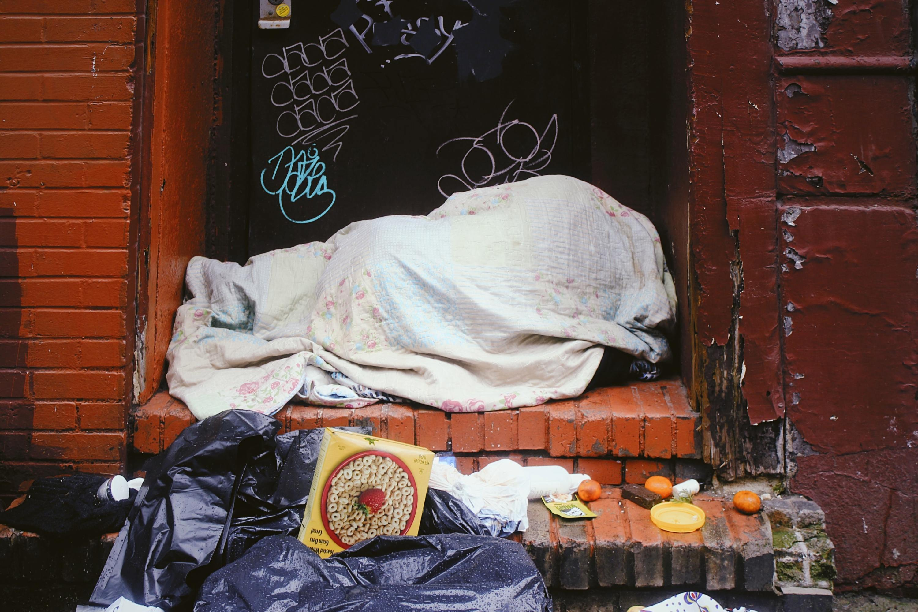 A homeless person bundled up on the street.