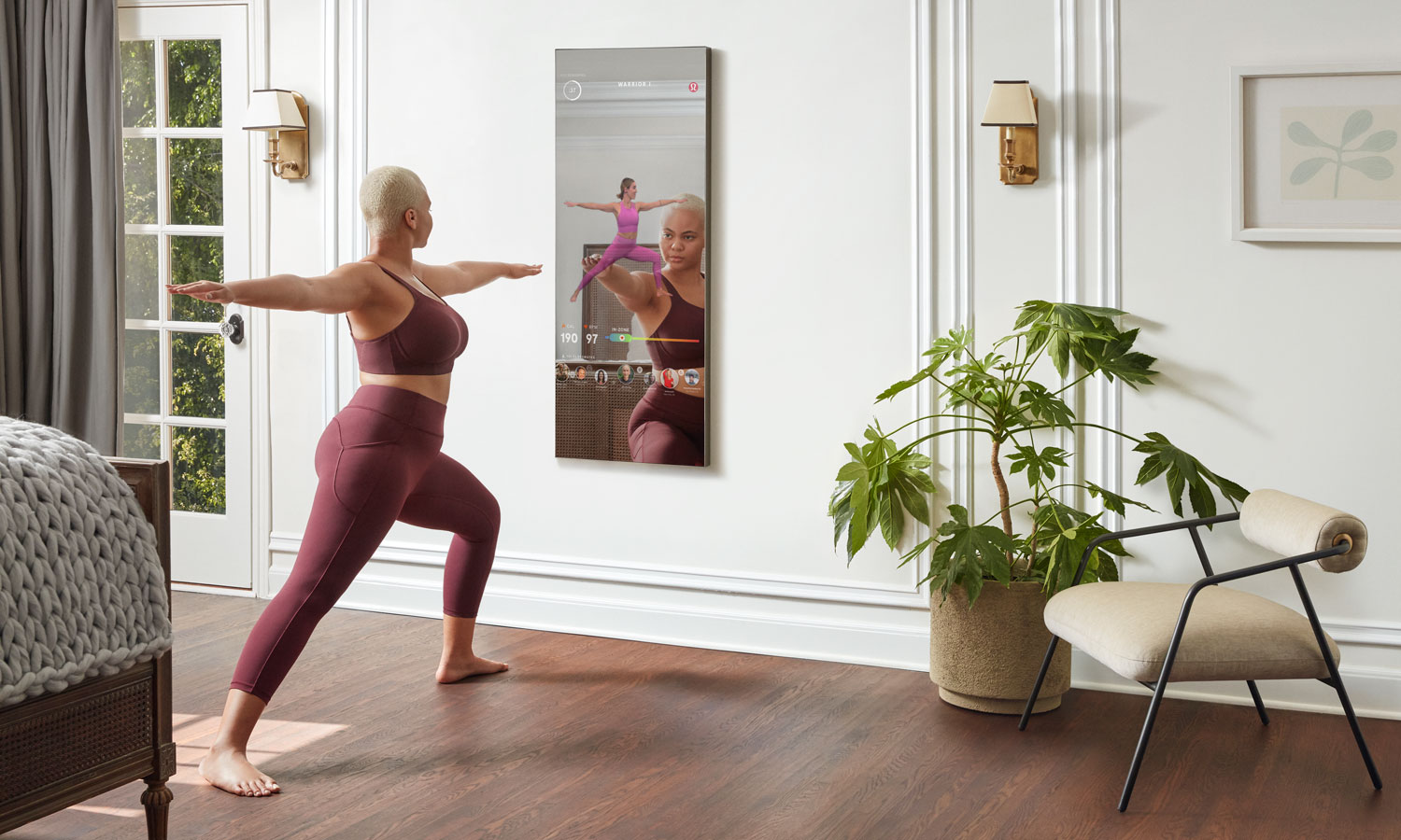 A woman doing yoga in warrior pose, in front of the Lululemon mirror, which gives her workout instructions.